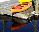 Kayak on a dock with reflection in the water.